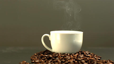 Steam rising from coffee cup on pile of coffee beans Footage