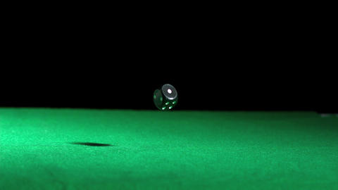 Black dice falling and bouncing on green table Footage