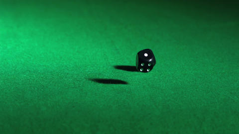 Black dice falling on green table Footage
