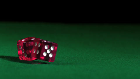 Pink dice falling and bouncing on green table Footage