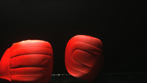 Red boxing gloves falling on black background Live Action