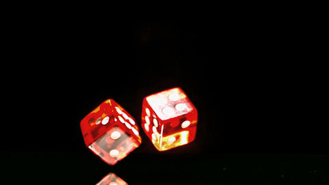 Two red dice falling and bouncing close up on blac Footage