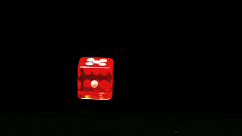 Red dice falling and bouncing close up on black background Live Action