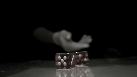 Hand throwing two dice onto table in black and whi Footage