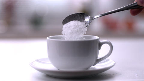 Pouring powdered sugar from teaspoon into a white  Footage