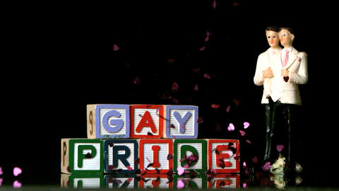 Confetti falling on blocks spelling gay pride with Footage