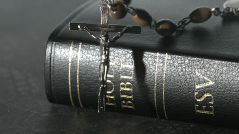 Rosary beads falling onto a bible Footage