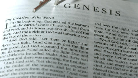 Rosary beads falling onto book of genesis Footage
