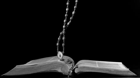 Rosary beads falling onto open bible Footage
