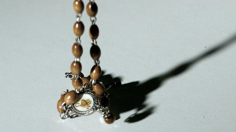 Rosary beads casting a shadow and then falling on  Footage