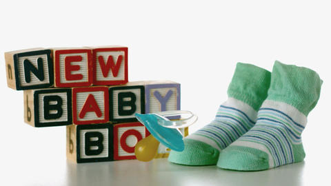 Blue soother falling besides slippers and baby blocks Live Action
