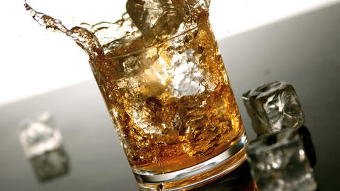 Ice falling into tumbler of whiskey and ice Footage