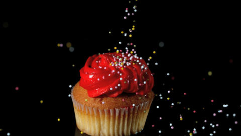 Sprinkles falling onto red iced cupcake Footage