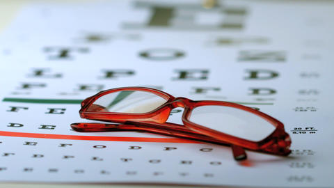 Reading glasses falling onto eye test Footage
