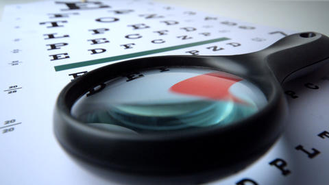 Magnifying glass falling over on eye test close up Footage