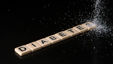 Sugar pouring over letter pieces spelling diabetes Footage