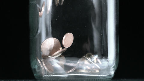 Many coins pouring into glass jar close up Footage