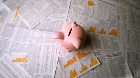 Pink piggy bank falling over sheets of paper Footage