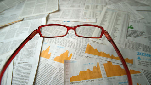 Glasses falling over sheets of paper showing yello Footage
