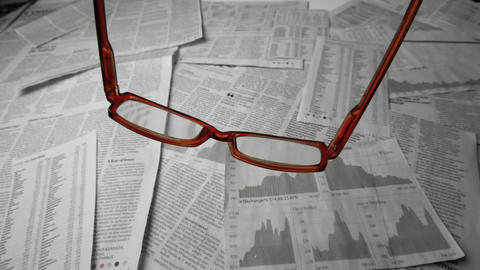 Glasses falling over sheets of paper showing graph Footage