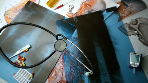 Stethoscope falling over x ray beside other medica Footage