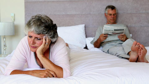 Woman worried about something while her husband is reading newspapers Footage