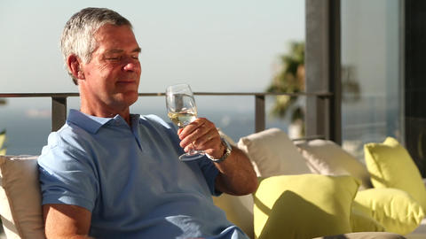Man drinking a glass of wine while sunbathing Footage