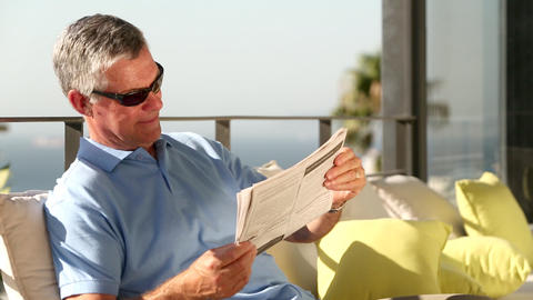 Mature man taking off his sunglasses while reading Footage