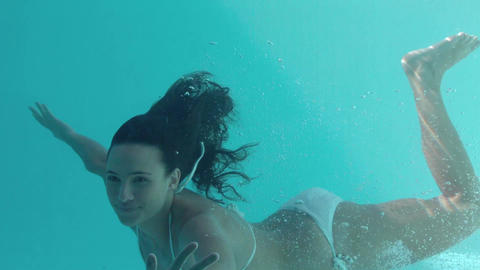 Smiling brunette swimming underwater and looking a Footage