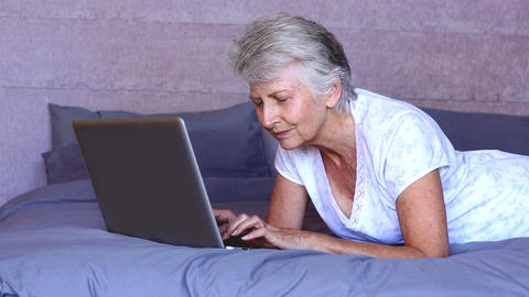 Woman Lying On Bed Using Laptop stock footage
