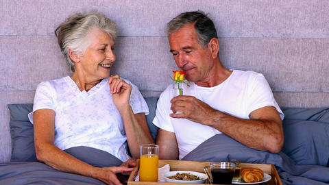 Elderly couple having breakfast in bed Footage
