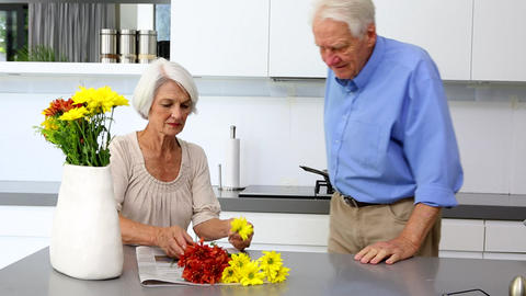Woman arranging flowers and holds one to husbands  Footage