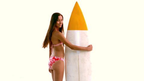 Woman next to her surfboard turning and looking at Footage