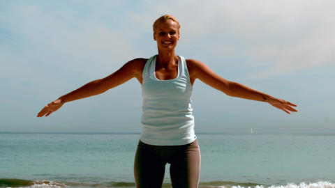 Sportswoman doing jumping jacks on the beach Footage