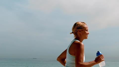 Sportswoman jogging across the beach Footage