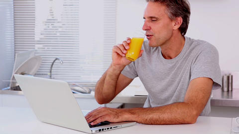 Mature man drinking orange juice while using his l Footage
