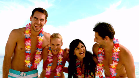 Friends wearing garlands and laughing on the beach Footage