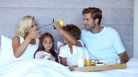 Family sitting in bed and having breakfast in bed Live Action