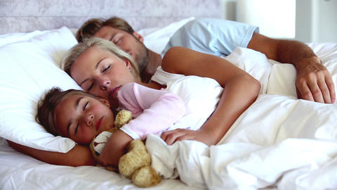 Parents and daughter holding teddy bear sleeping p Footage