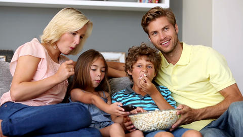 Family eating popcorn and watching tv together Footage