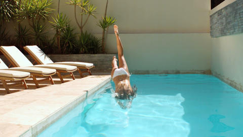 Attractive woman diving into swimming pool Footage