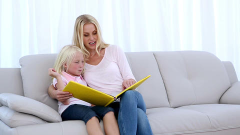 Mother and daughter reading a book together Footage
