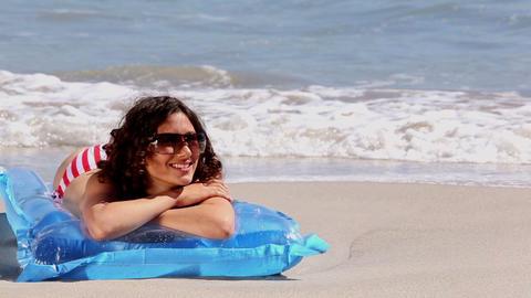 Girl sunbathing on a lilo on the beach Footage