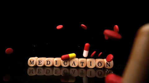 Pills falling and rolling over dice spelling medic Footage
