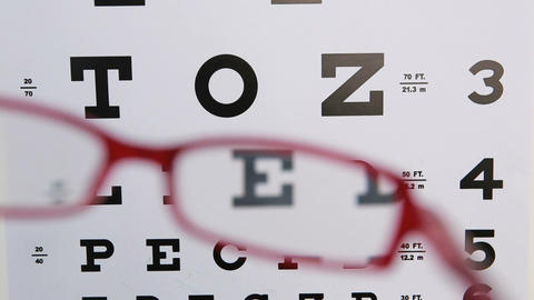 Red glasses held up to read eye test Footage