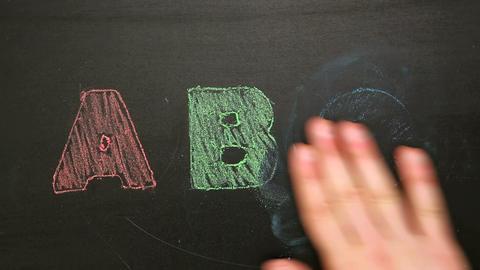 Hand rubbing off abc drawn on chalkboard Footage