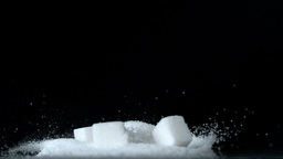Sugar cubes falling down into pile of sugar on black background Live Action