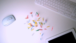 Colourful paperclips falling on office desk Footage