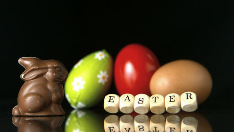 Dice spelling out easter falling in front of easter treats and egg Footage