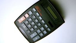 Black calculator falling on white surface Footage